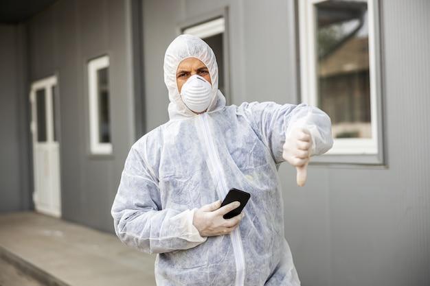 Mann im virenschutzanzug und in der maske, die auf handy-smartphone suchen und tippen, gebäude des coronavirus mit dem sprühgerät desinfizierend. epidemie. weltpandemi