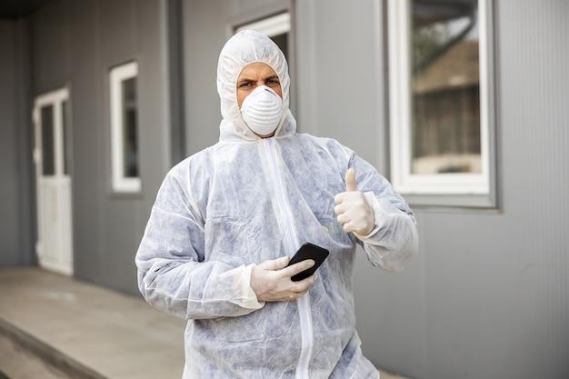 Mann im virenschutzanzug und in der maske, die auf handy-smartphone suchen und tippen, gebäude des coronavirus mit dem sprühgerät desinfizierend