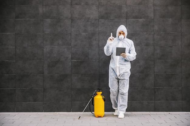 Mann im virenschutzanzug und in der maske, die auf tablette schauen und tippt, gebäude von covid-19 mit dem sprühgerät desinfizierend. infektionsprävention und seuchenbekämpfung. weltpandemie.