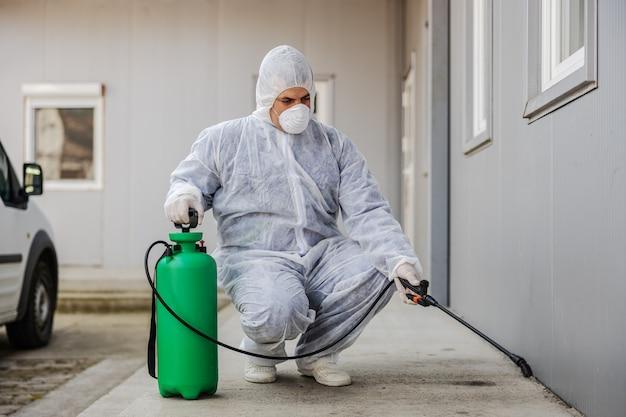 Mann im virenschutzanzug und maske desinfizieren gebäude des coronavirus mit dem sprühgerät. epidemie.