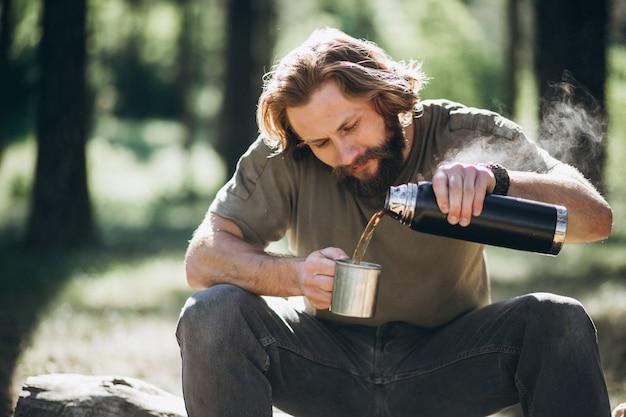 Mann im wald mit tee durch feuer