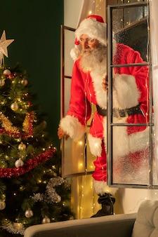 Mann im weihnachtsmannkostüm, das durch das fenster ins haus kommt