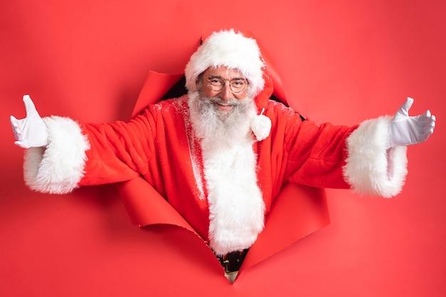 Mann im weihnachtsmannkostüm, das durch papier herauskommt