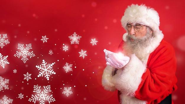 Mann im weihnachtsmannkostüm, das schneeflocken bläst