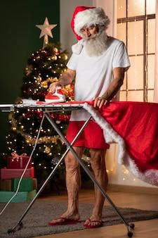 Mann im weihnachtsmannkostüm mit bügelbrett