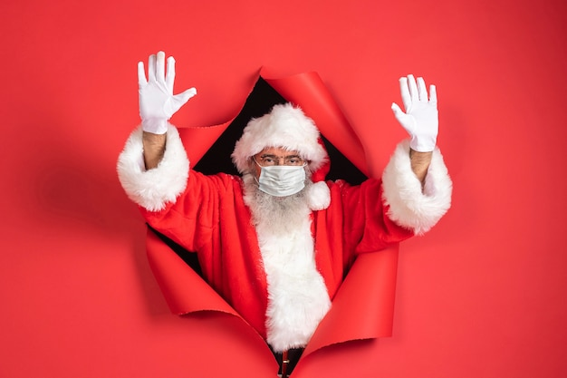 Mann im weihnachtsmannkostüm mit der medizinischen maske, die aus papier kommt