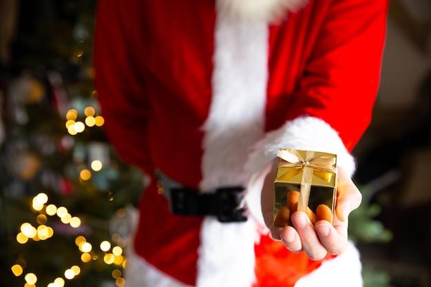 Mann im weihnachtsmannkostüm nahe weihnachtsbaum, der eine goldene geschenkbox hält