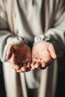 Mann im weißen gewand streckt seine hand aus, friedenssymbol. sohn gottes, christlicher glaube, gebet