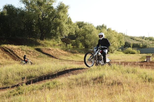 Mann im weißen helm, der motorrad auf unebenem gelände reitet, während bergab auf spur bewegt wird