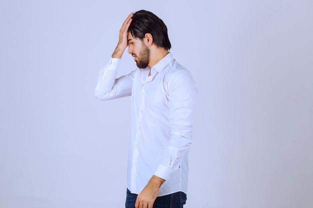 Mann im weißen hemd bedeckt sein gesicht, fühlt sich traurig und hat kopfschmerzen.