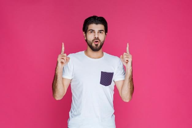 Mann im weißen hemd, das auf etwas oben zeigt.