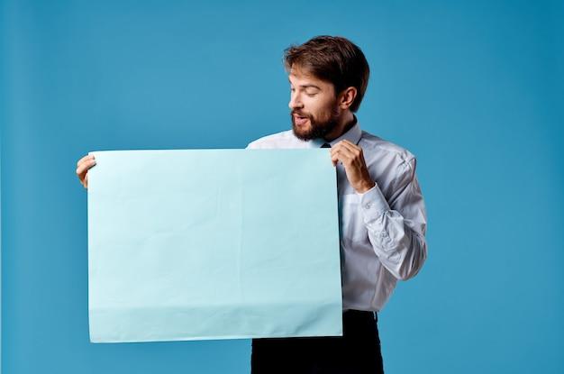 Mann im weißen hemd, das banner in den händen emotionen hält, die blauen hintergrund vermarkten. hochwertiges foto