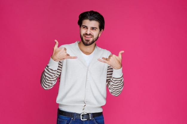Mann im weißen hemd, das daumen oben handzeichen macht.