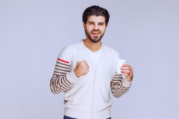 Mann im weißen hemd, das eine kaffeetasse hält und es genießt.