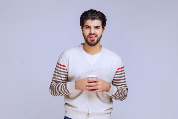 Mann im weißen hemd, das eine tasse kaffee hält und hat.