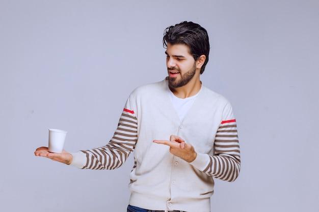Mann im weißen hemd, das eine wegwerfbare kaffeetasse hält.