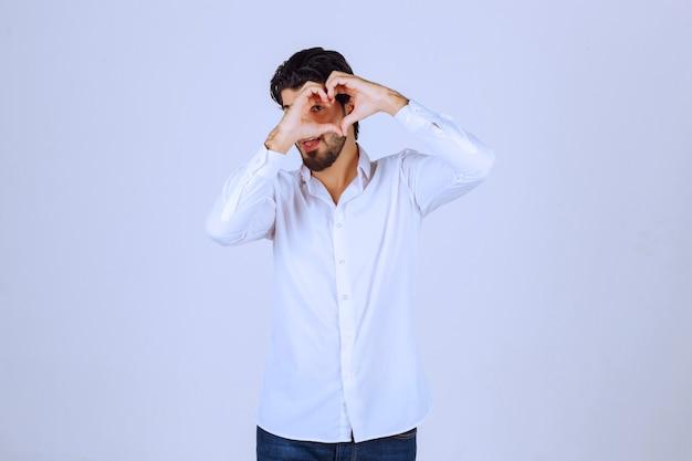 Mann im weißen hemd, das liebe zu seinen fans bläst.
