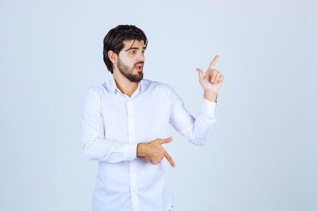 Mann im weißen hemd, das nach oben zeigt.
