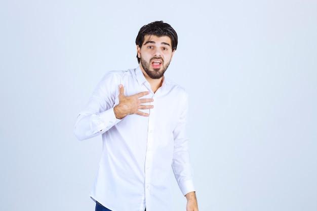 Mann im weißen hemd, der auf sich selbst zeigt