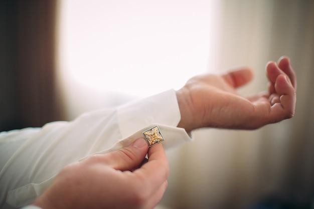 Mann im weißen hemd, der einen bolzen befestigt. konzept eines morgens des jungen mannes.