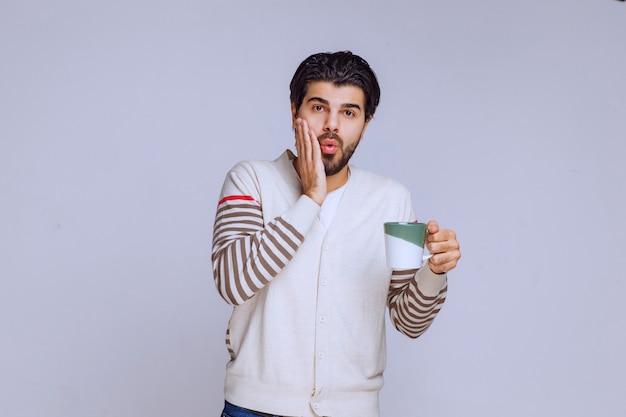 Mann im weißen hemd hält eine kaffeetasse und sieht überrascht aus.