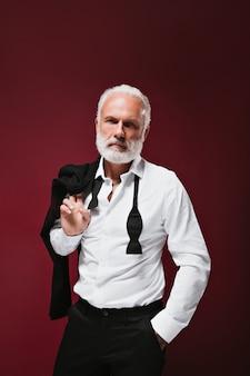 Mann im weißen hemd hält schwarze jacke