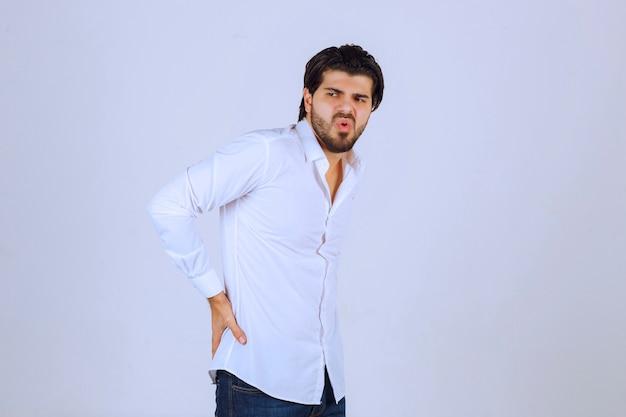 Mann im weißen hemd hat rückenschmerzen.