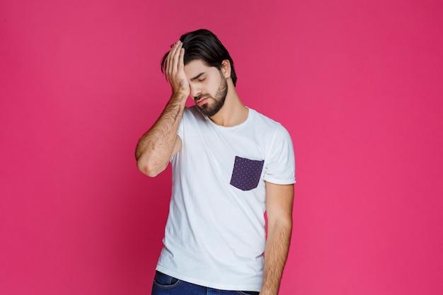 Mann im weißen hemd kann sich nicht davon abhalten, auf füßen zu schlafen.