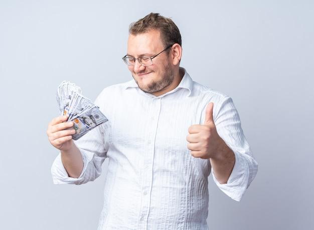 Mann im weißen hemd mit brille, der bargeld glücklich und positiv hält und daumen nach oben über weißer wand zeigt