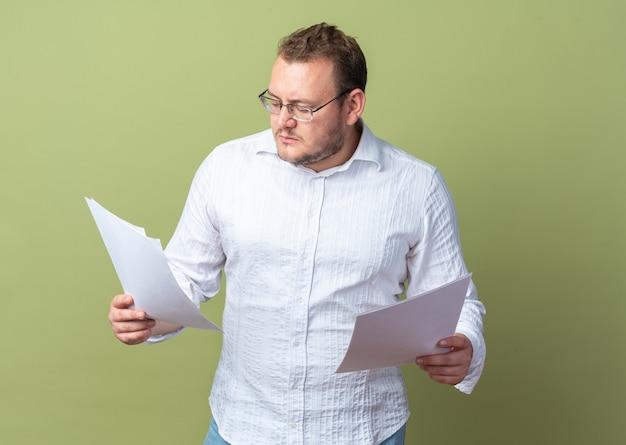 Mann im weißen hemd mit brille, der dokumente hält, die sie mit ernstem gesicht betrachten, das über grüner wand steht?