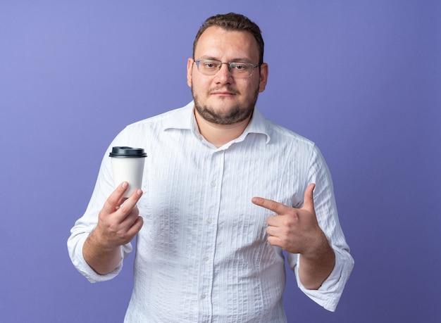 Mann im weißen hemd mit brille, der eine kaffeetasse hält und mit dem zeigefinger darauf zeigt, lächelt selbstbewusst über blauer wand?