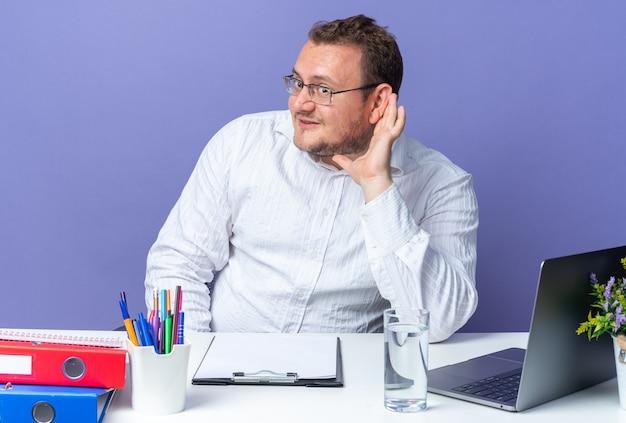 Mann im weißen hemd mit brille, der glücklich und positiv beiseite schaut, mit der hand über dem ohr, der versucht, am tisch mit laptop und büroordnern über blauer wand zu hören, die im büro arbeiten