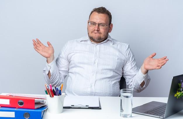Mann im weißen hemd mit brille, der nach vorne schaut, verwirrt die arme zu den seiten, die am tisch sitzen, mit laptop-büroordnern und zwischenablage über weißer wand, die im büro arbeitet