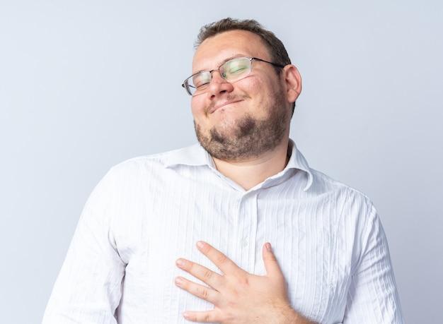 Mann im weißen hemd mit brille glücklich und zufrieden auf sich selbst lächelnd zeigend
