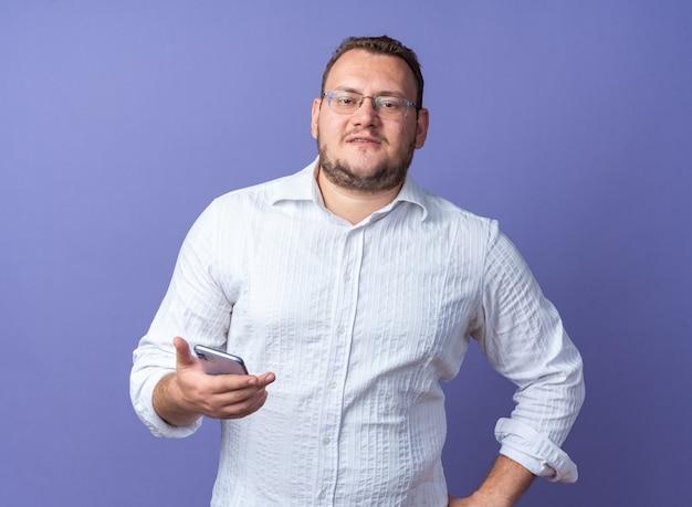 Mann im weißen hemd mit brille hält smartphone und lächelt selbstbewusst über blauer wand