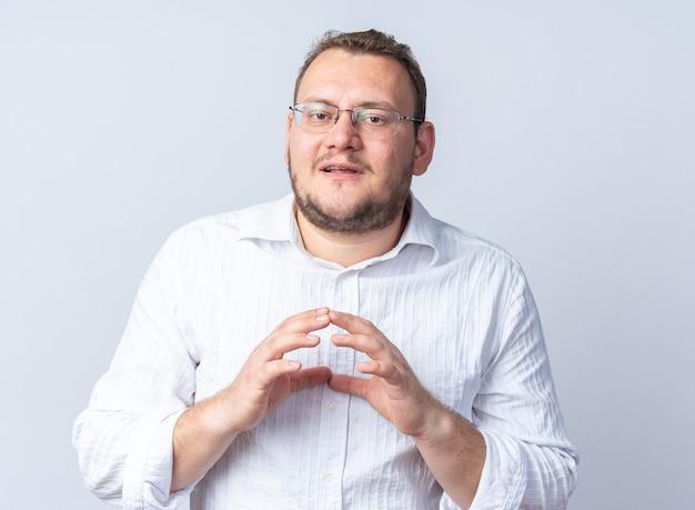 Mann im weißen hemd mit brille sieht selbstbewusst lächelnd aus und hält die hände zusammen und wartet auf etwas