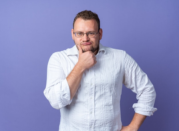 Mann im weißen hemd mit brille und hand am kinn, der mit nachdenklichem ausdruck über blauer wand steht