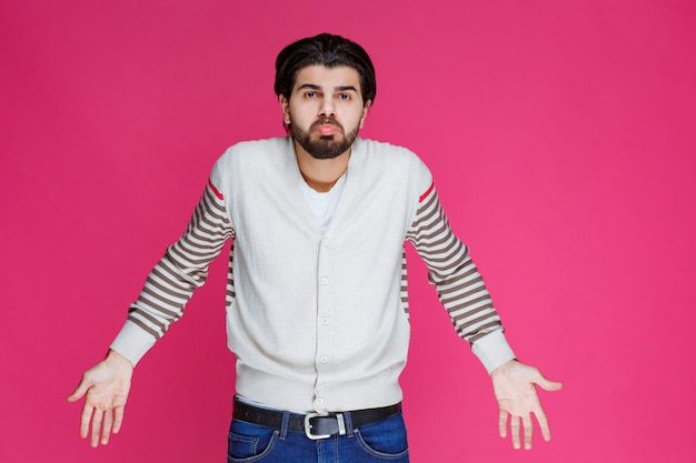 Mann im weißen hemd sieht verwirrt und verloren aus.