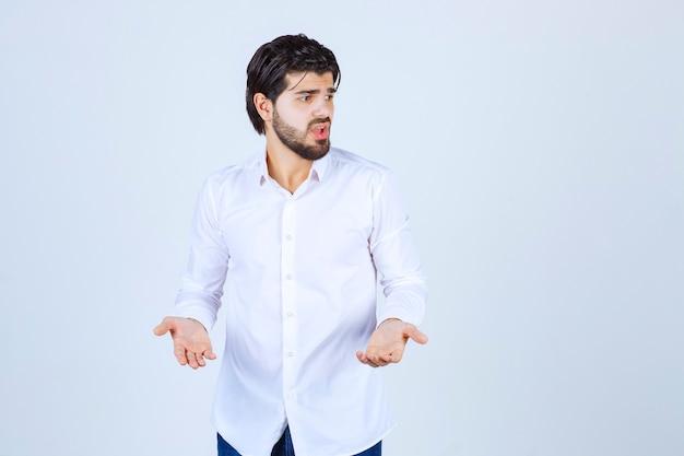 Mann im weißen hemd sieht verwirrt und verloren aus