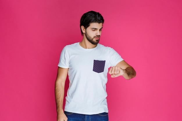Mann im weißen hemd überprüft seine zeit.