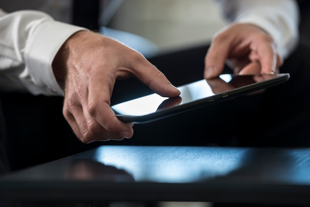 Mann im weißen hemd unter verwendung einer tablette
