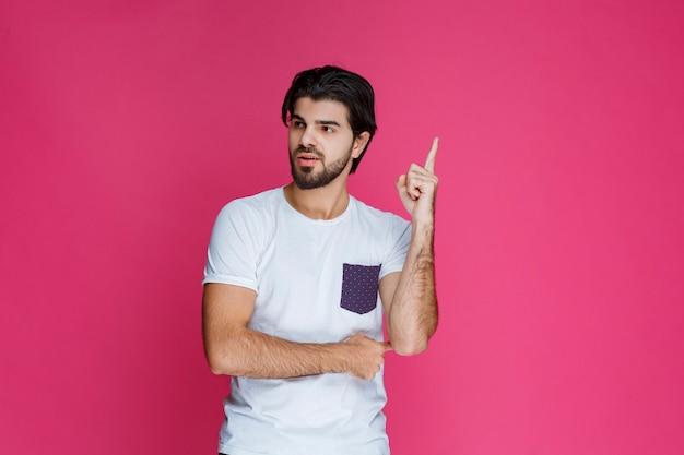 Mann im weißen hemd zeigt und präsentiert etwas über seinem kopf.