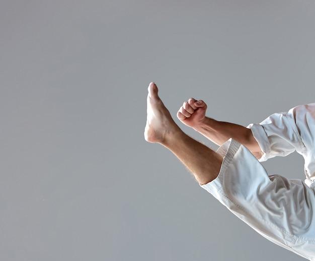 Mann im weißen kimono, der karate über grauem hintergrund trainiert. nahaufnahme von arm- und beinathleten während des aufpralls