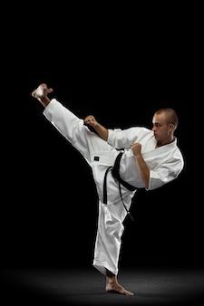 Mann im weißen kimono und im schwarzen gürtel, der karate über grauem hintergrund trainiert.