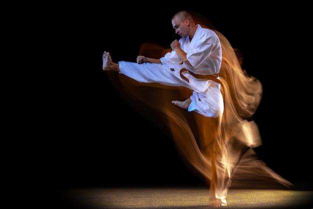 Mann im weißen kimono und im schwarzen gürtel, der karate über schwarzem studiohintergrund trainiert.