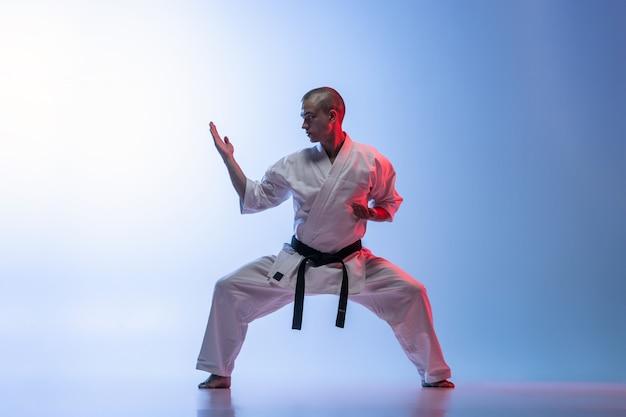 Mann im weißen kimono und im schwarzen gürtel, der karate über weißem hintergrund ausbildet.