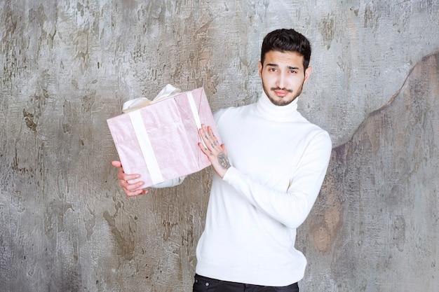 Mann im weißen pullover, der eine lila geschenkbox hält, die mit band eingewickelt wird.