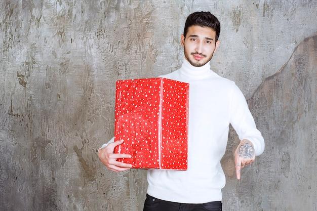 Mann im weißen pullover, der eine rote geschenkbox mit weißen punkten darauf hält und jemanden neben sich einlädt