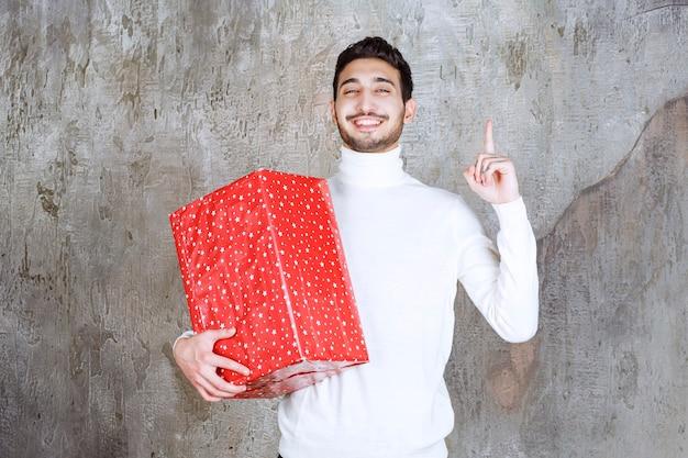 Mann im weißen pullover hält eine rote geschenkbox mit weißen punkten drauf