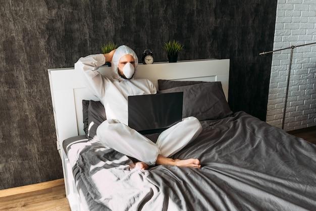 Mann im weißen schutzkostüm mit kapuze und gesichtsmaske zu hause auf dem bett mit laptop